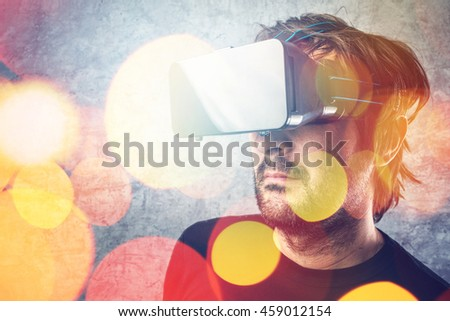 Adult man wearing virtual reality goggles and watching 3D VR multimedia content, modern futuristic technology gadget