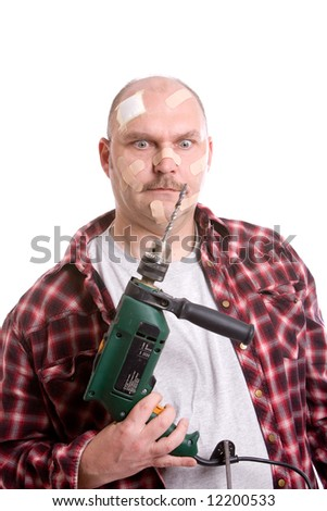 Adult man with a dril looking frustrated at the machine in his hand, his face covered in bandaids - stock photo
