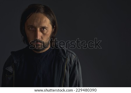 Adult man with beard in black jacket, low key portrait - stock photo
