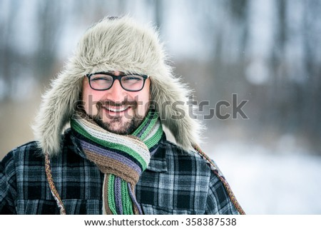 Adult man with beard wearing glasses. The man smiles. Winter, snow, a man in a fur hat.