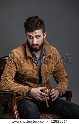Adult man with black hair and beard sitting on chair with cigar and whiskey while looking at camera - stock photo
