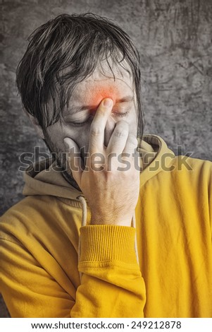 Adult Man with Chronic Sinus Headache Wearing Yellow Jacket, conceptual image with selective desaturation. - stock photo