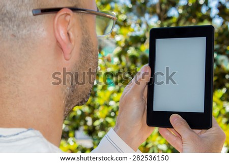 adult man with glasses reading an e-book in a garden - stock photo