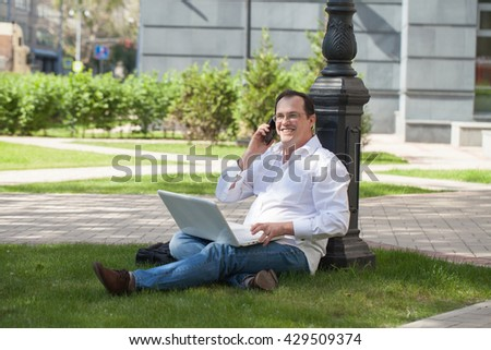 Adult man with laptop and mobile phone sitting on the grass