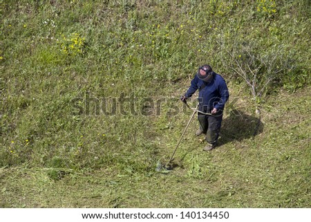 Adult man with lawn mower trimming grass in the field - stock photo