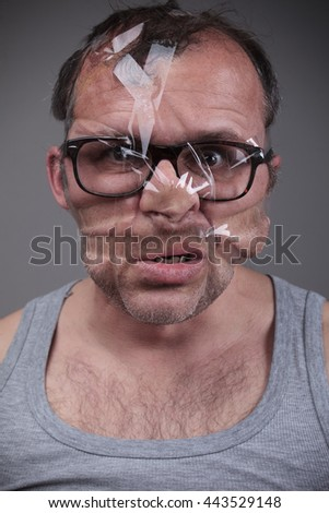 Adult man with taped face, portrait over gray background - stock photo