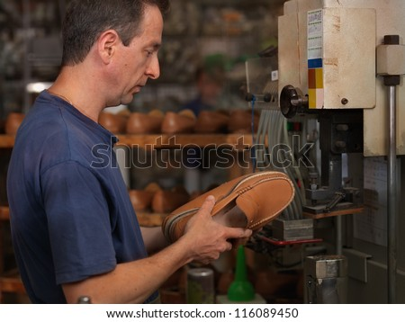 adult man working in a shoe factory, checking the quality of the products