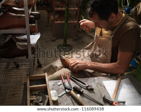 adult man working in a shoe factory, sewing the soles of the shoes manually - stock photo