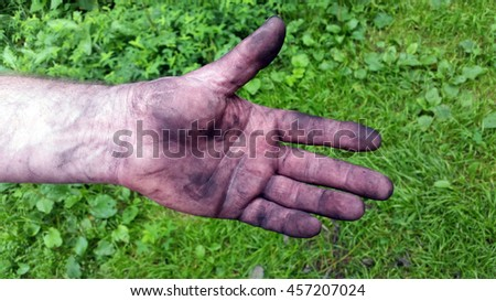 Adult men's hand smeared with charcoal, dirt and dust - stock photo