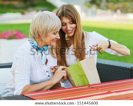 Adult mother and daughter are considering buying after shopping. They are sitting in a cafe outside. - stock photo