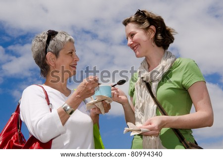 Adult mother and daughter share ice cream in cup outdoors with a blue sky and white clouds for a background - stock photo