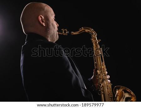 Adult musician playing tenor saxophone, dark background