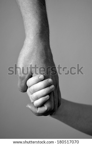 Adult or parent holding the hand of a small child - stock photo
