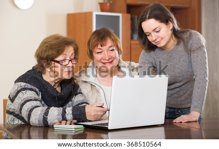 adult pensioners and young relative making shopping list on laptop - stock photo