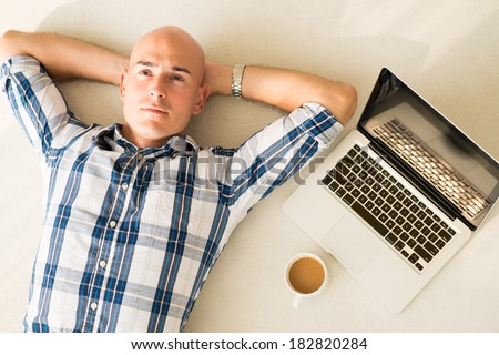 Adult pensive businessman lying on the floor near laptop and coffecup viewed below  - stock photo