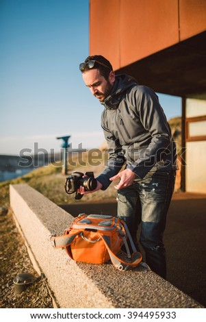 Adult photographer preparing his equipment to a shooting outdoors