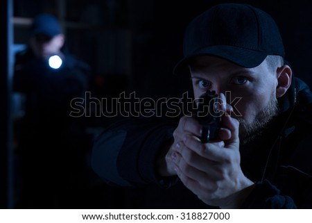 Adult police officer pointing gun at criminal - stock photo