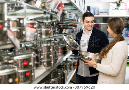 adult positive american  couple chooses pans in shop cookware. focus on man - stock photo