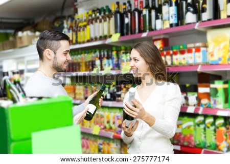 Adult positive european shoppers choosing bottle of wine at liquor store - stock photo