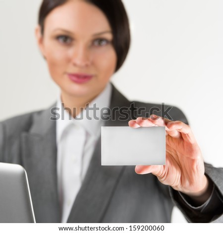 Adult pretty businesswoman working with laptop at her office and holding blank business card at foreground. Focus on card - stock photo