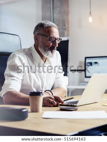 Adult professional businessman wearing a classic glasses and working at the wood table in modern coworking studio.Stylish bearded middle age man using laptop on workplace. Vertical,blurred