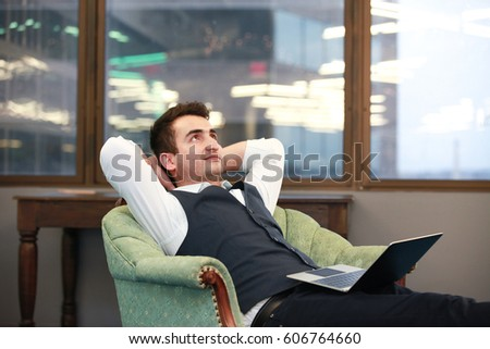 Adult relaxed businessman sitting with laptop in armchair in Arlington city, Virginia.