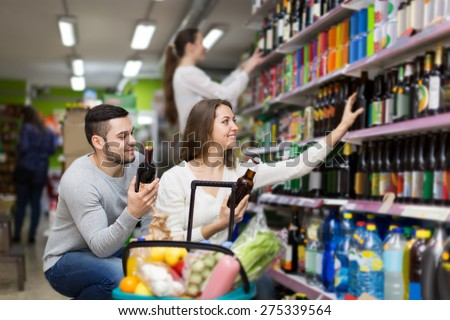 Adult russian shoppers choosing bottle of wine at liquor store - stock photo