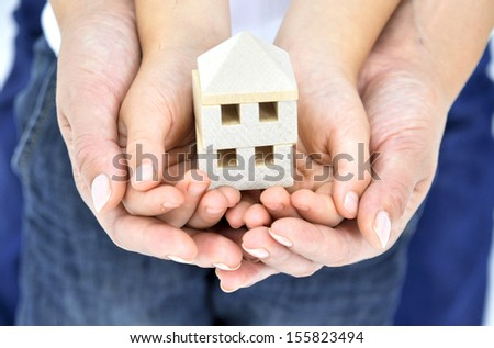 Adult's Hand holding Child's Hands and wooden House - stock photo