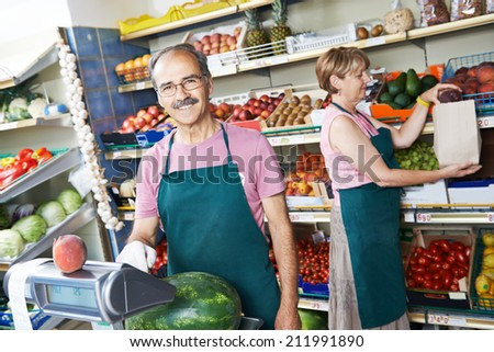 adult senior sale man with assistant in fruit vegetable market shopping store - stock photo