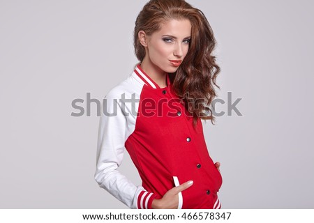 adult sensuality brunette cheerleader woman girl , white and red baseball jacket isolated on grey background