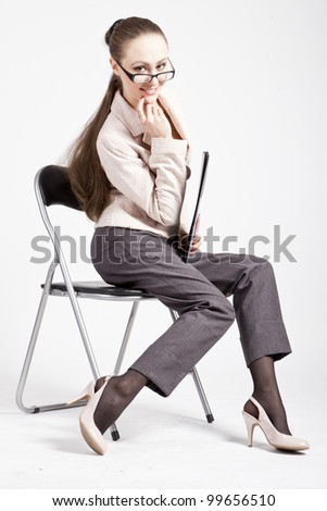 adult sexy girl sitting on a chair holding folder, smiling - stock photo