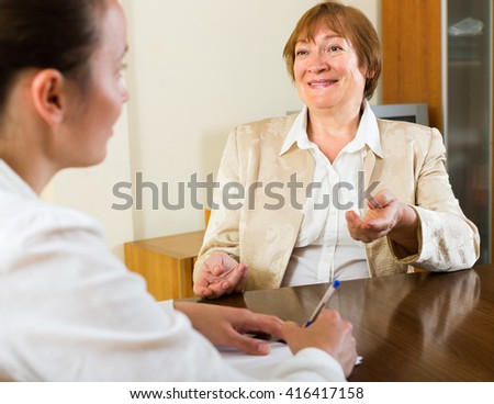 Adult smiling women talk cheerfully about something - stock photo