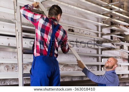 Adult smiling workmen choosing PVC window profile at factory - stock photo