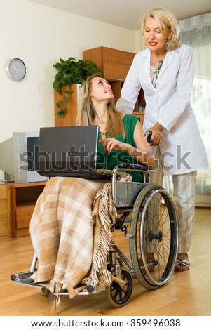 Adult social worker and disabled young woman on chair with laptop. Focus on girl - stock photo