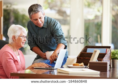 Adult Son Helping Mother With Laptop - stock photo