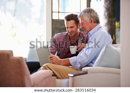 Adult Son Helping Senior Father With Computer At Home - stock photo