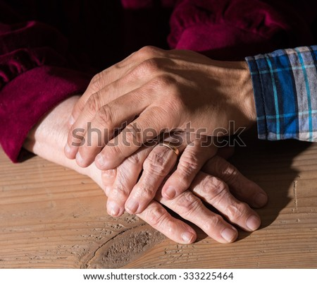 Adult son holding mothers senior hands at home on a wooden background