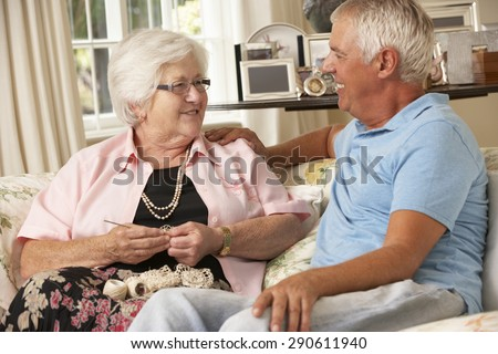 Adult Son Visiting Senior Mother Sitting On Sofa At Home Doing Crochet - stock photo