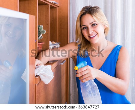 adult spanish woman in casual cleaning at home and smiling