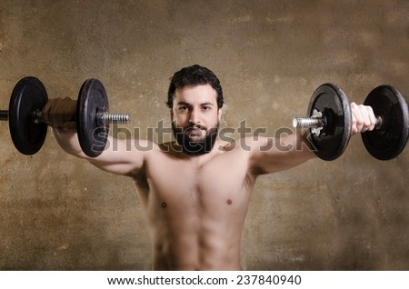 Adult spartan shirtless hipster man lifting weights