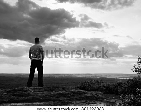 Adult sportsman on the cliff in rocky mountains park and watch into landscape. Black and white photo
