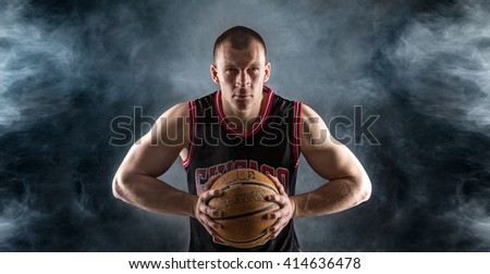 Adult sportsman with basketball ready to throw a ball. Smoke, black background