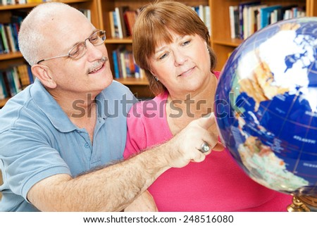 Adult students in library using a globe to study geography.   - stock photo
