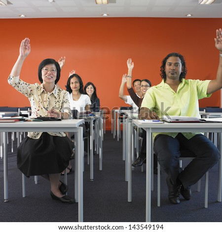 Adult students raising hands in classroom