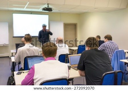 adult students sitting in a classroom, using laptop computers during class