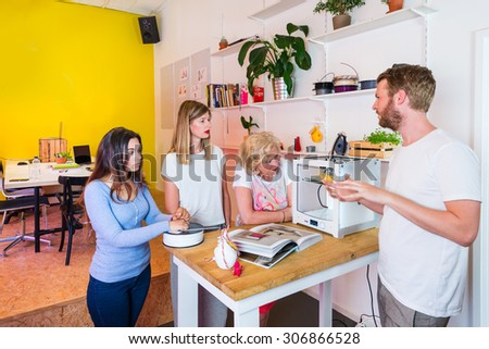 Adult students standing around a 3D printing machine during an in-company workshop, with a tutor explaining the possibilities of this new technology - stock photo