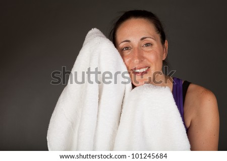 Adult sweating woman with towel after a workout - stock photo