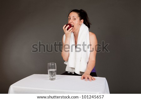 Adult sweating woman with towel after a workout eating an apple with a glass of water