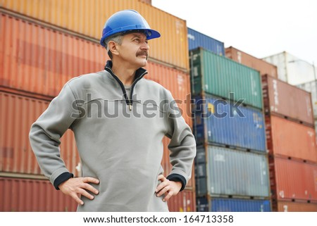 adult terminal cargo dock warehouse worker in front of maritime shipping container - stock photo