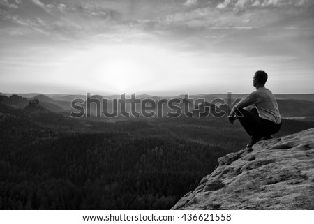 Adult tourist in black trousers, jacket sit on cliff's edge and looking to misty hilly valley bellow. Hiker relax and thinking alone in nature.